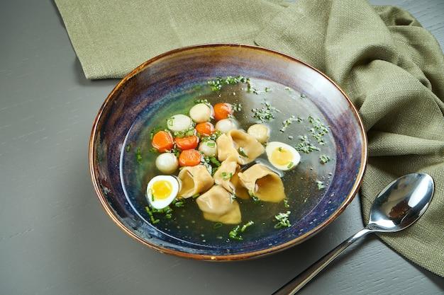 木製のテーブルの青いボウルにラビオリとゆで野菜の食欲をそそるチキンスープ。ランチにイタリア料理