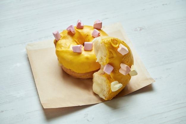 木製のテーブルのクラフトペーパーに黄色のアイシングとマンゴーの充填で食欲をそそるドーナツ。ドーナツを切る。クラシックなアメリカンデザートペストリー