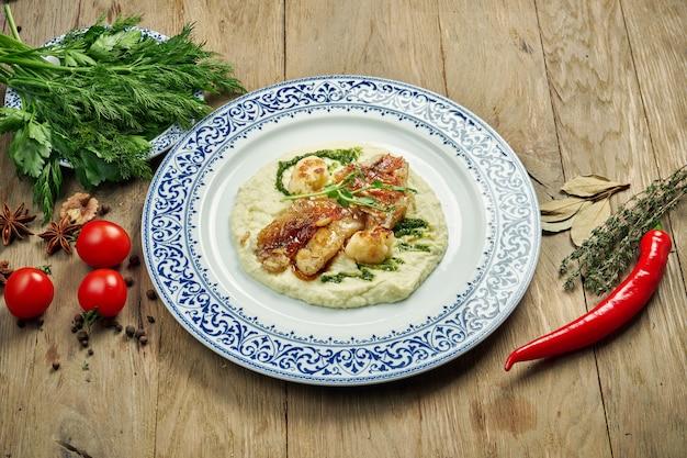 Жареное филе окуня с пюре из цветной капусты в белой тарелке на деревянном столе. вкусные морепродукты с гарниром