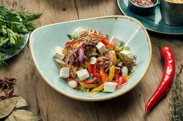 Классический греческий салат с помидорами, луком, огурцом, сыром фета и маслинами в белой тарелке на деревянном столе. крупным планом зрения. еда плоская планировка