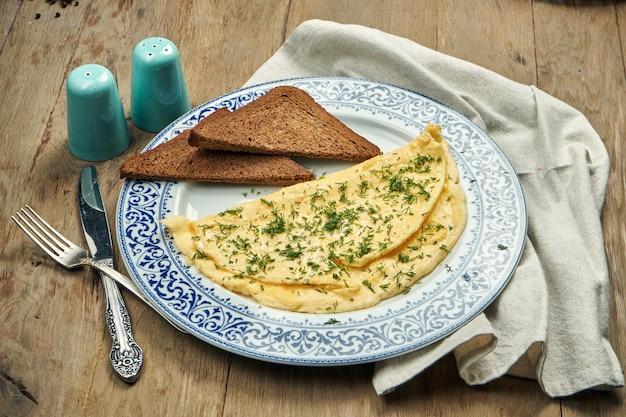 食欲をそそる朝食-木製のテーブルのセラミックプレートにグリーンとライ麦トーストのオムレツ。