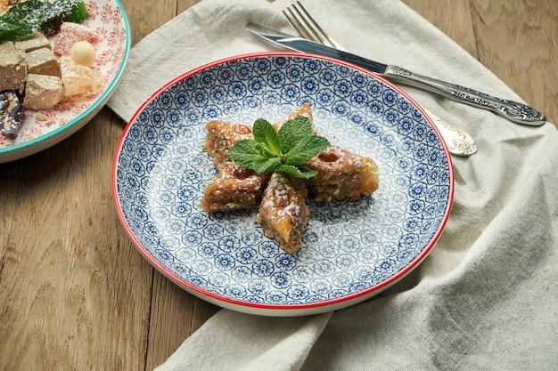 ピスタチオと木製のテーブルのセラミックプレートに蜂蜜と古典的なトルコのバクラヴァ。トルコのペストリーやお菓子。閉じる