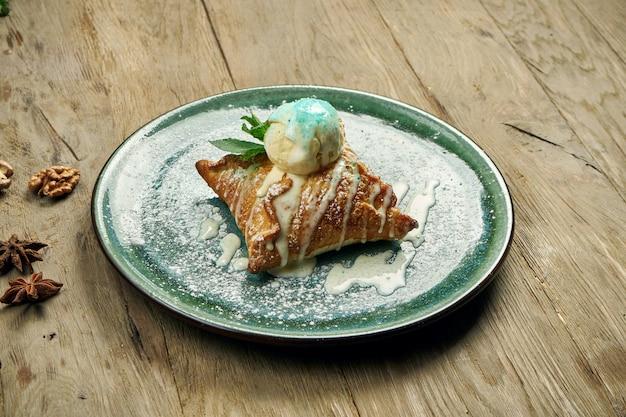 木製のテーブルのブループレートにバニラアイスクリームとアップルシュトルーデル。人気のオーストリアのペストリーとデザート。閉じる