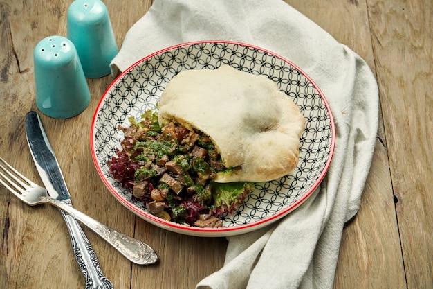 おいしい屋台の食べ物-トマト、キュウリ、牛肉と木製のテーブルの上の青い味付けのピタ。ギリシャ料理。ビューを閉じます。シュワルマ