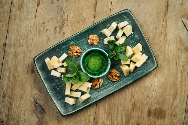 前菜-チーズプレート。セラミックプレートの異なる自家製チーズ-ブリー、カマンベール、蜂蜜とナッツを使ったオランダ料理。ワイン前菜。