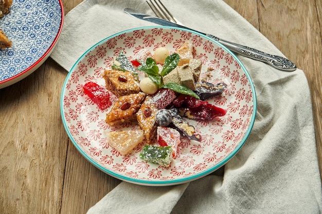 Классические восточные сладости - пахлава с медом и орехами, лукум, чурчхела в красной керамической тарелке на деревянном столе