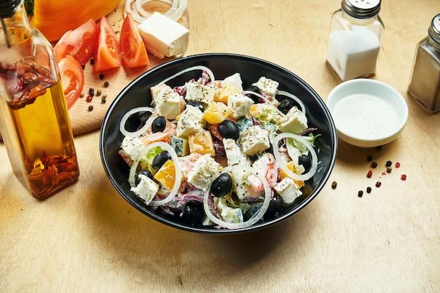 Классический греческий салат с помидорами, луком, огурцом, сыром фета и маслинами в черном шаре на деревянном столе. крупным планом зрения. еда плоская планировка
