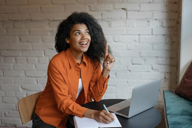 若い興奮ビジネス女性の指を持ち、アイデアを持って、自宅で仕事