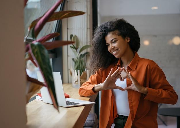 ラップトップを使用した成功したブロガーインフルエンサー、オンラインでの加入者とのコミュニケーション