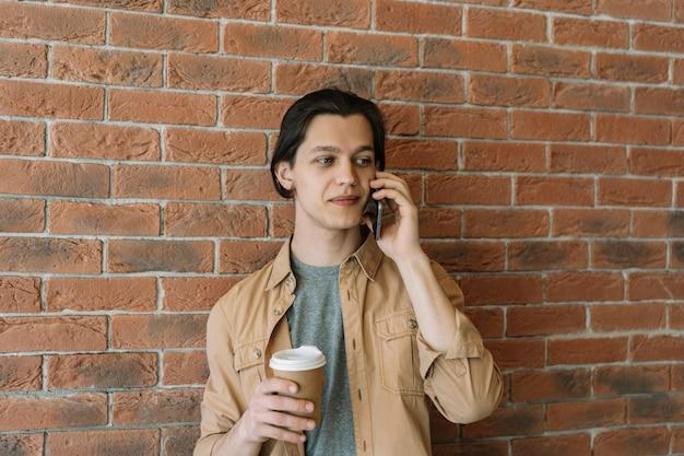 一杯のコーヒーを保持している携帯電話で話している若い魅力的な男