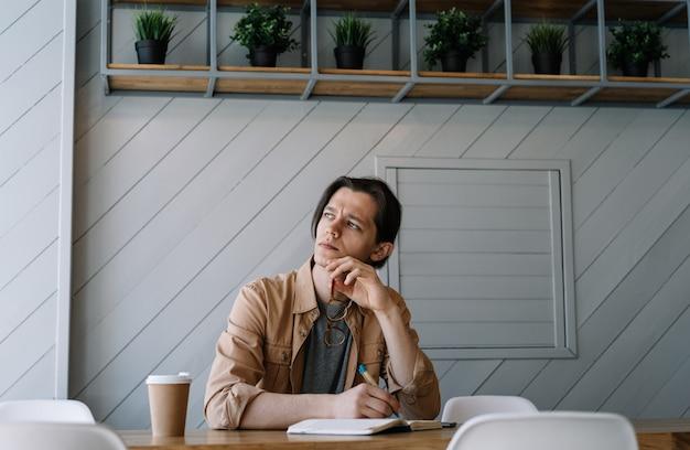 物思いにふける男がメモを書いたり、考えたり、ブレーンストーミングをしたり、自宅で仕事をしたり