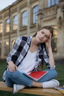 試験結果に失望した学生。試験の失敗、ベンチに座って疲れた顔で不幸な女性
