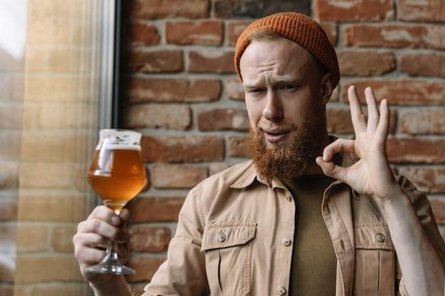 Бородатый мужчина пьет пиво в пабе. битник парень, держа бокал с алкоголем, дегустация пива, расслабляющий, показать знак ок