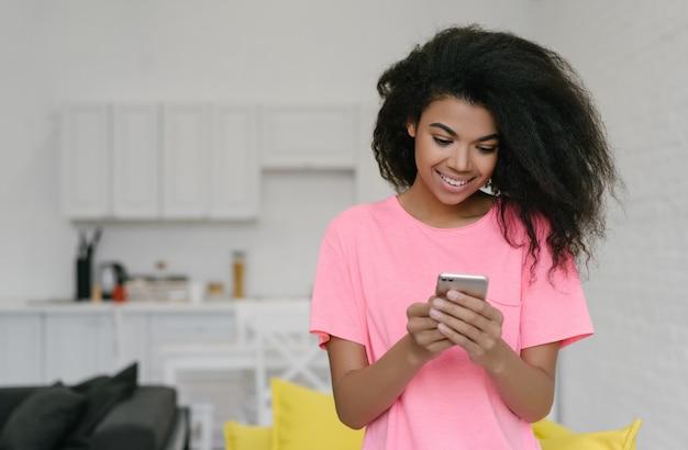 Красивая усмехаясь афро-американская женщина держа мобильный телефон, заказывая еду, онлайн покупки, остается дома. эмоциональная девушка битник с помощью смартфона, бронирование билетов, общение