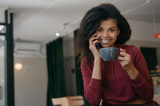 モダンなカフェでコーヒーを飲みながら、スマートフォン、コミュニケーションを保持している若い美しい女性。コーヒーブレイク