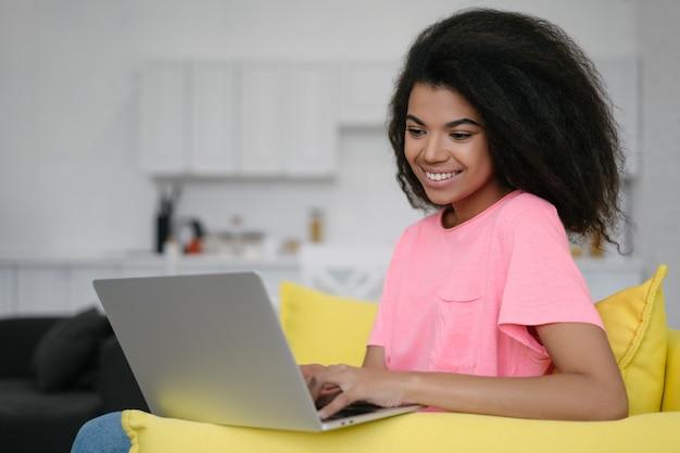 Портрет счастливой афро-американской женщины копирайтер работает внештатный проект онлайн, сидя у себя дома. удачного бизнеса и карьеры. хипстер девушка, используя портативный компьютер, набрав на клавиатуре