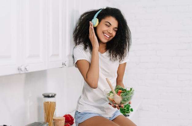 美しいアフリカ系アメリカ人女性が台所でベジタリアンディナーを調理します。健康的なライフスタイルのコンセプトです。新鮮なサラダとフクロウを押し、自宅で音楽を聴く、笑って幸せな感情的な女の子