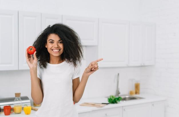 コピースペースに指を指しているトマトを保持している美しい笑顔のアフリカ系アメリカ人女性。健康的なライフスタイルのコンセプト、ベジタリアン、ダイエット。魅力的な女の子が新鮮な夕食を調理し、キッチンに立っています。