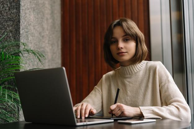 写真家は、ラップトップとドローイングタブレットを使用して、職場で画像をレタッチします。
