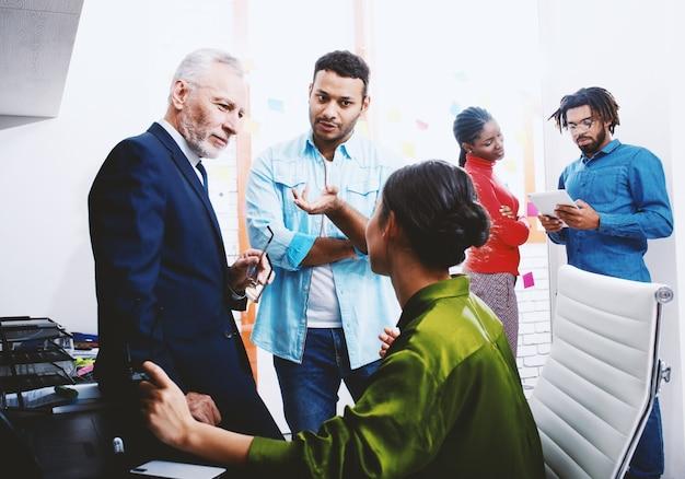オフィスで一緒に働くビジネスマン。チームワークとパートナーシップの概念