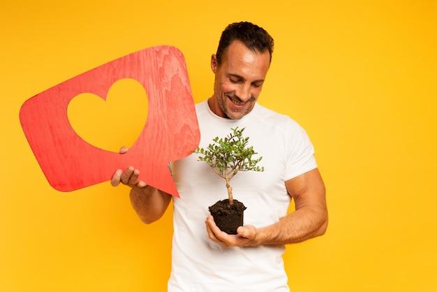 幸せな男は、植える準備ができている小さな木が好きです。植林のコンセプト