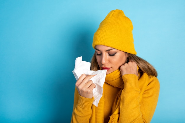 女の子は風邪をひいて鼻を拭いた。シアンの背景