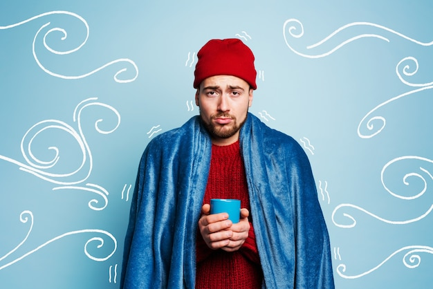 Мальчик простудился и пьет горячую пищу. голубой фон. концепция болезни