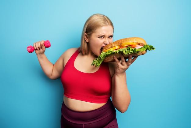 Полная девушка занимается спортом и хочет съесть бутерброд. понятие нерешительности и сомнения