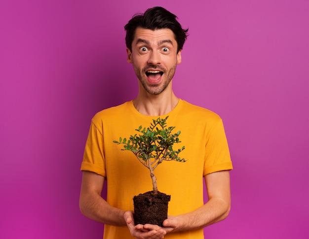 幸せな少年は、明るい色の上に植える準備ができている小さな木を保持しています。植林、生態学および保全の概念