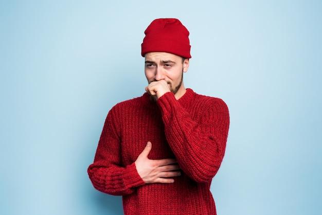 Мальчик простудился и имеет кашель. студия на голубом фоне
