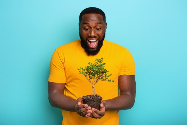 幸せな驚いた少年は植えられる準備ができている小さな木を保持します。植林のコンセプト