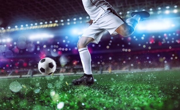試合中にスタジアムでサッカーボールを蹴る準備ができているサッカー選手。