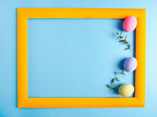 Красочные яйца в оранжевой рамке на синем фоне