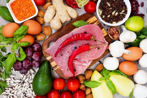 健康的な栄養の概念。バランスの取れた健康的なダイエット食品の背景。新鮮な有機野菜、果物、豆、肉、魚、乳製品。上面図。料理の材料。自然食品。晴れて食べる。元気