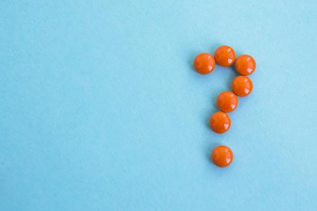 Вопросительный знак, сделанные оранжевые таблетки на синем фоне. творческая медицина для здоровья / проблемы со здоровьем, лекарственное взаимодействие, лекарственная ошибка и фармацевтическая концепция.
