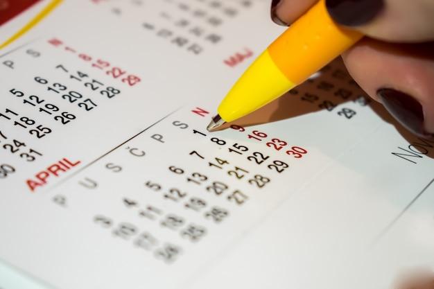 Ручная женщина, проверка плана собрания в фоне календаря.