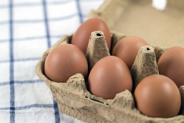 開いた卵のカートンの茶色の鶏の卵のオーバーヘッドビュー。新鮮な