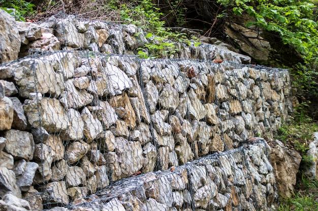 道の横にある擁壁。蛇籠壁のスチールメッシュ。