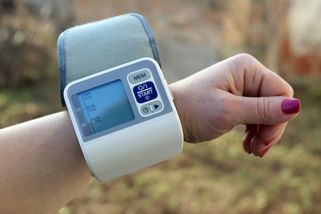 Женщина заботится о здоровье с монитором ритма очага и кровяным давлением