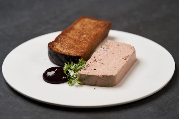 コピースペースと暗い背景に白い皿にパテとトーストしたパン、クローズアップ。