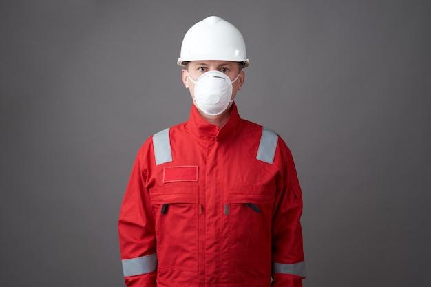 若いエンジニアの労働者は、ヘルメット、フェイスマスクを着用します。