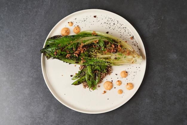 Ромейн на гриле с зеленой фасолью, киноа и соусом из копченой паприки на белой тарелке