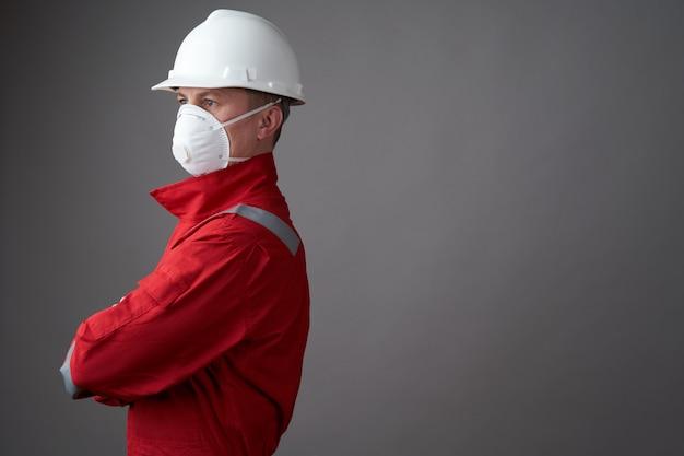 衛生的なマスク、全体的および保護ハード帽子を身に着けている労働者の男