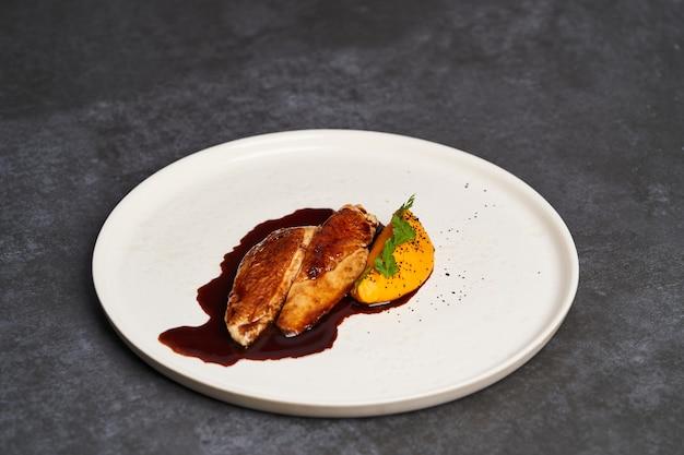 マッシュした若いニンジンとチキンジュースが添えられた鶏の胸肉