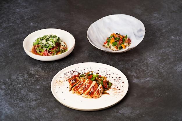 コピースペースを持つ灰色のテーブル背景に食品のさまざまなプレートのセット