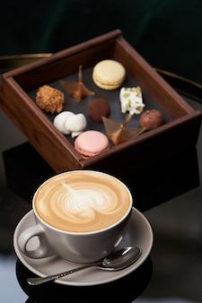 一杯のカプチーノコーヒーとテーブルの上の木箱にチョコレート菓子