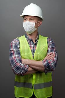 衛生的なマスクと保護ヘルメットを身に着けている労働者の男。