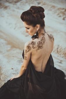 手と少女の背中にヘナで一時的な刺青を描く
