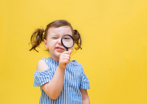 ポニーテールの少女が虫眼鏡でのぞきます。縞模様のブラウスを着たかわいい女の子が虫眼鏡をのぞきます。黄色の空間に虫眼鏡を持つ少女。フリースペース。