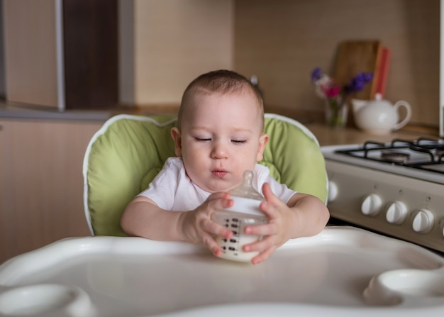 男の子は摂食椅子に座っているし、ボトルから飲み物